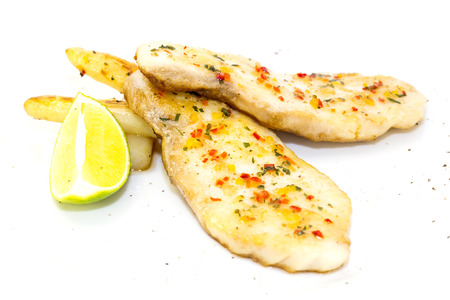 sturgeon steak cooking on the grill with lemon and sauce on a table in a restauran photo