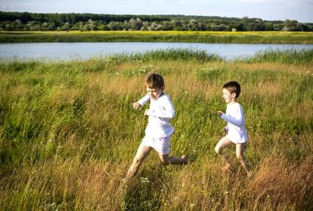 boy running on the field in summer photo