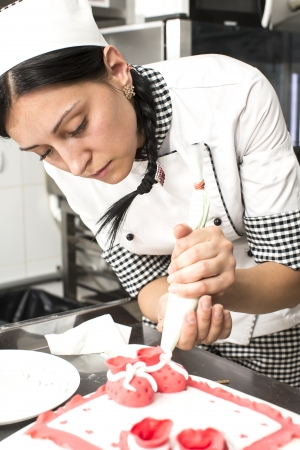 sweet pastries: pastry chef decorates a cake in a candy store Stock Photo