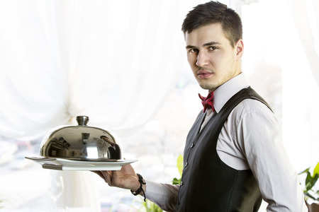 waiter with a tray of food in the restaurant hall photo