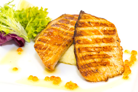 Grilled salmon fillet with vegetables and caviar photo