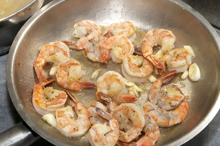 cooking shrimp in a pan in the kitchen at the restaurant photo