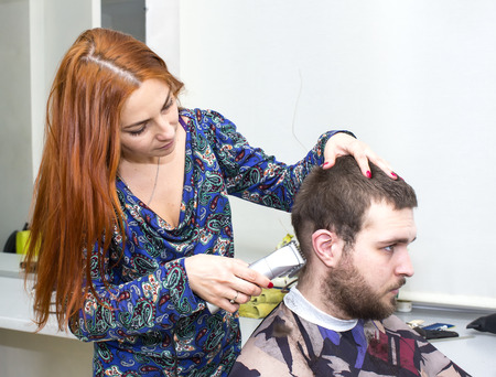 girl doing hairstyle at the guy photo