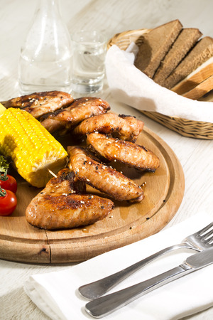 chicken wings are grilled on a wooden platter photo
