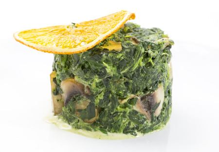 appetize: fried spinach decorated with a slice of orange Stock Photo