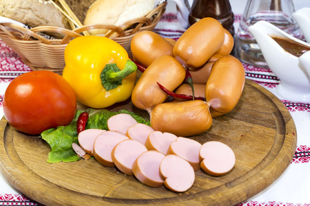 sausages on a wooden plate with vegetables in a restaurant photo