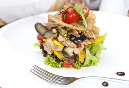 warm salad of vegetables and meat on a plate in a restaurant photo