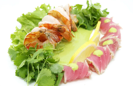 shrimp and tuna with greens and sauce on a white background photo