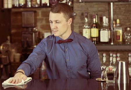 young man working as a bartender in a nightclub bar Archivio Fotografico