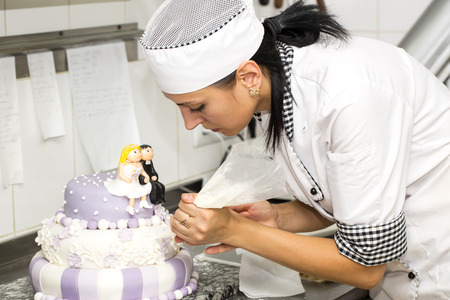 pastry chef decorates a cake in a candy store Stock Photo