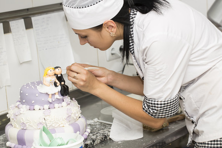pastry chef decorates a cake in a candy store photo