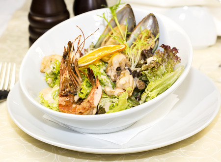 salad with vegetables and seafood on the table in a restaurant photo