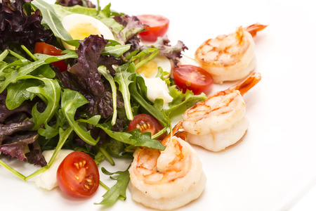 good cholesterol: salad greens and shrimp on a white background in the restaurant Stock Photo