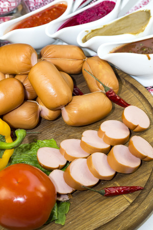 uncooked bacon: sausages on a wooden plate with vegetables in a restaurant Stock Photo