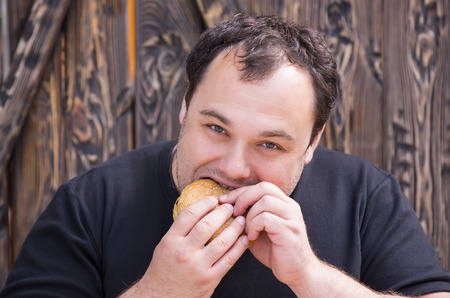 brutal man eating a hamburger photo