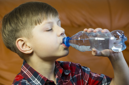 qua: boy drinks water from a plastic bottle Stock Photo