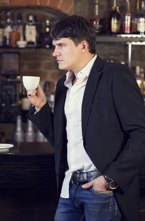 hombre tomando cafe: hombre bebiendo caf� cerca de la barra Foto de archivo