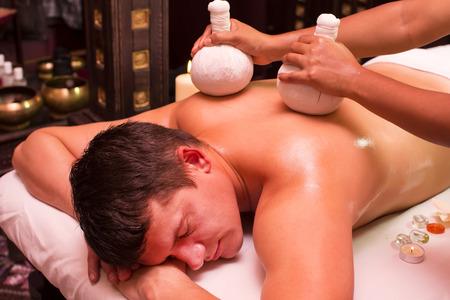 herbal massage ball: man engaged in Ayurvedic spa treatment