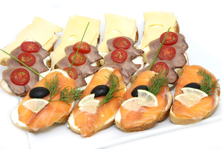 girdle: Canapes of cheese vegetables meat and seafood on white background Stock Photo