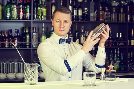 young man working as a bartender in a nightclub bar Фото со стока