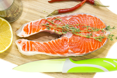 raw salmon steak with lemon and spices on a cutting board photo