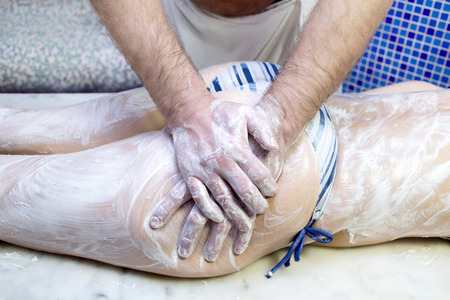 easing: processes facials male masseur makes women in the hammam Stock Photo