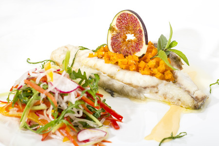 stuffed fish: Baked fish with salad on a white background in restaurant