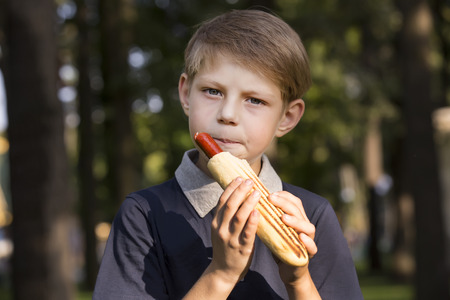 boy eating a hot dog on the street