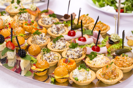 Canapes of cheese vegetables meat and seafood on white background Фото со стока