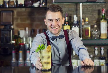 young man working as a bartender in a nightclub bar 写真素材