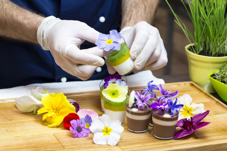 cook prepares canapes dessert edible flowers and buds