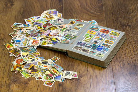 old album: stamps with old album on the table Stock Photo