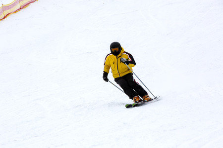 Snowboarder coming down the mountain in bad weather on a snowboard