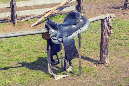reigns: saddle for riding a horse on a wooden fence ranch Stock Photo