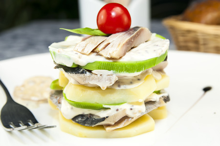 Herring salad with avocado sauce on a plate in a restaurant photo