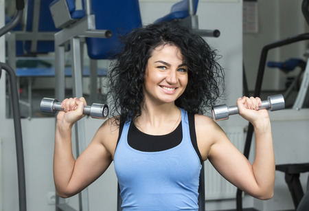 muscle gain: young girl engaged in bodybuilding in the gym