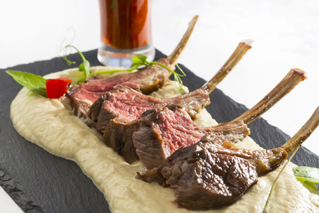 rack of lamb: lamb ribs cooked on the grill served on a hot stone