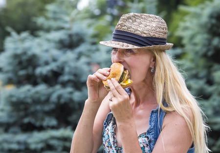 hippie woman: adult woman hippie woman eating a hamburger