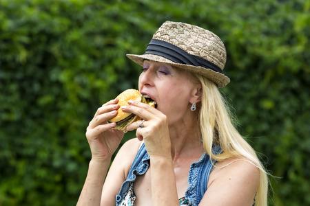 mujer hippie: mujer adulta mujer hippie comer una hamburguesa Foto de archivo