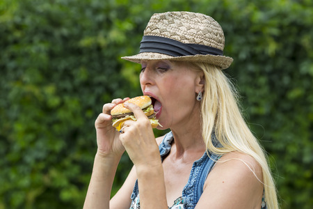mujer hippie: adult woman hippie woman eating a hamburger
