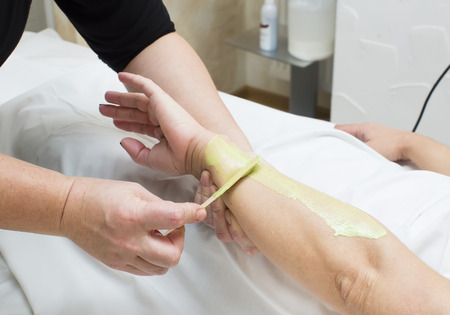 depilate: Woman in a beauty salon doing depilation