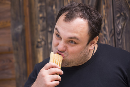 eating fast food: man eating a hot dog on the background wall