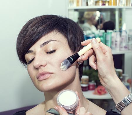 visagiste: Make-up artist in the studio doing makeup beauty girl
