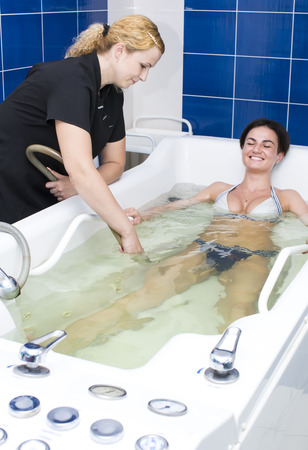 hydromassage: doctor makes a woman a massage at hydrobath