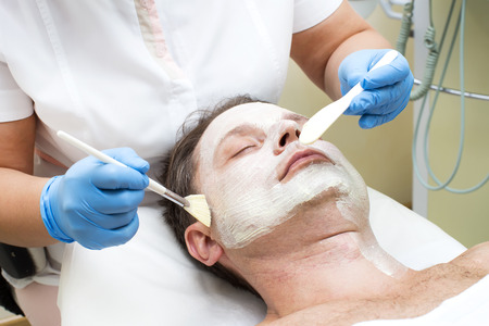 facial spa: man in a beauty salon facial and massage