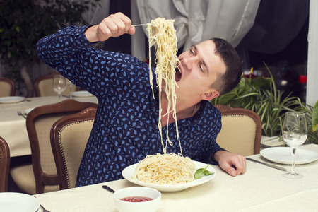 man eating a large portion of pasta in a restaurant