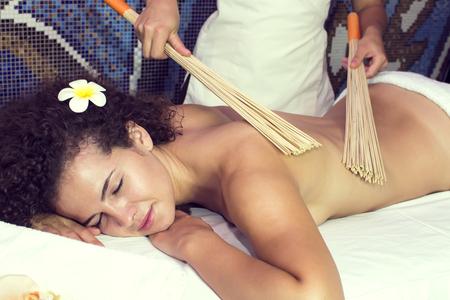 massage: Japanese massage with bamboo sticks in the spa salon Stock Photo