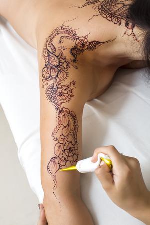 mehendi: mehendi drawing process in a beauty salon