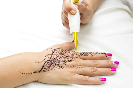 mehendi: mehendi drawing process in a beauty salon