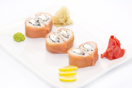 sushi: plate of sushi beautifully decorated with salad and fruit on a white background Stock Photo